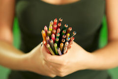 Young female painter holding colored pencils at camera Stock Photography