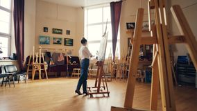 Young female painter is painting picture indoors working inside light workshop alone. Wooder easels, authentic artworks stock video footage