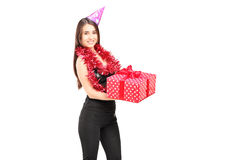 A young female with party hat standing and holding a gift Royalty Free Stock Images