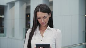 Young female passenger at the airport terminal, using her tablet computer while waiting for her flight. Young female passenger at the airport, using her tablet stock footage