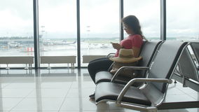 Young female passenger at the airport, using her phone while waiting for her flight. Young female passenger at the airport, using her tablet computer while stock video footage