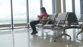 Young female passenger at the airport, using her phone while waiting for her flight. Young female passenger at the airport, using her tablet computer while stock video