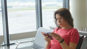 Young female passenger at the airport, using her phone while waiting for her flight. Young female passenger at the airport, using her tablet computer while stock footage