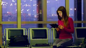 Young female passenger at the airport, using her. Tablet computer while waiting for her flight stock footage