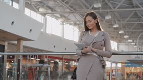 Young female passenger at the airport using her tablet computer while waiting for flight stock footage