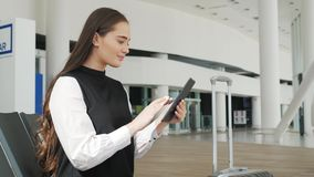 Young female passenger at the airport, using her tablet computer while waiting for her flight, smiling, sunnu day. Young female passenger at the airport, using stock footage