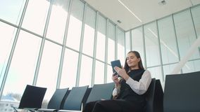 Young female passenger at the airport, using her tablet computer while waiting for her flight, smiling, sunnu day. Young female passenger at the airport, using stock video footage