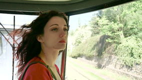 Young female passenger inside the train looking out the window on the road. Portrait of sensual brunette woman with stock video footage
