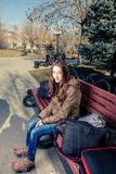 Young female passenger resting on park bench with Royalty Free Stock Images