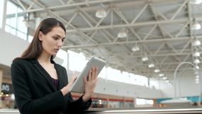 Young female passenger traveller at the airport using her tablet computer while waiting for flight, business woman after stock video footage