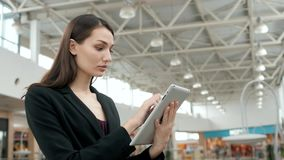 Young female passenger traveller at the airport using her tablet computer while waiting for flight, business woman after stock footage