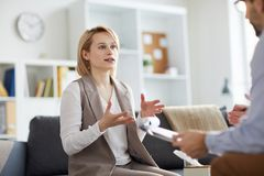 Visiting counselor. Young female patient in casualwear explaining what bothers her during conversation with psychologist stock photo