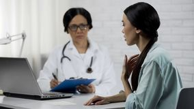 Young female patient saying symptoms, experienced doctor keeping medical records stock image
