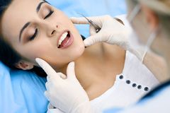 Young female patient visiting dentist office.Beautiful woman with healthy straight white teeth sitting at dental chair stock photo
