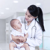 Young female pediatrician holding a baby Stock Image