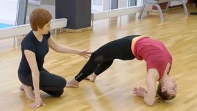 Young female performs asana with trainer in fitness center. Beautiful woman is engaged in yoga under supervision of professional in modern studio. Brunette is stock video footage