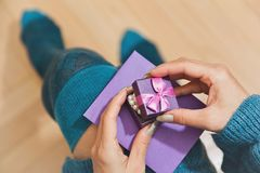 Female person in stockings unpacking gift. Young female person in blue dress and stockings unpacking a gift holding it on her knees with a envelope. Birthday Stock Photo