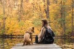 Girl hiker rests at riverbank with her pet dog and drinks coffee from thermos royalty free stock photos