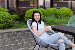 Young female person sitting in chair at cafe near green plants and drinking coffee. Concept of leisure time and resting Stock Photos