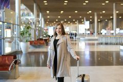 Young female person wearing grey coat walking in airport hall. Young female person wearing grey coat walking in airport hall with valise. Concept of traveling Stock Images