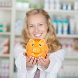 Young Female Pharmacist Holding Piggybank Stock Image
