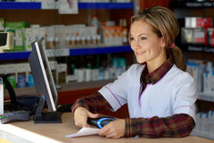 Young female pharmacist holding prescription Royalty Free Stock Photos