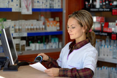 Young female pharmacist holding prescription Stock Image