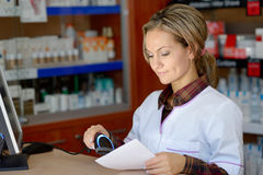 Young female pharmacist holding prescription Royalty Free Stock Images