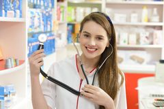 Young female pharmacist holding a stethoscope Royalty Free Stock Images