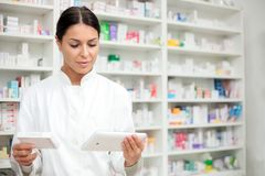 Young female pharmacist holding a tablet and box of medications stock photos