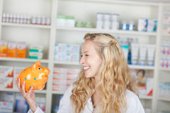 Young Female Pharmacist Looking At Piggy Bank Stock Images