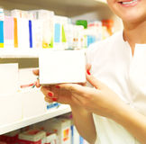 Young female pharmacist showing medicine box at pharmacy counter Royalty Free Stock Images