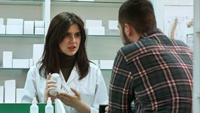 Young female pharmacist suggesting medical drug to male buyer in pharmacy drugstore. Close up. Professional shot in 4K resolution. 081. You can use it e.g. in Royalty Free Stock Photos