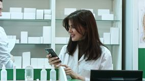 Young female pharmacist texting messages using mobile phone, smiling and talking to her male colleauge stock footage