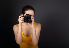 Young female photograph in yellow top holding camera and makeing Royalty Free Stock Images