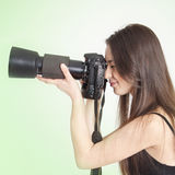 A young female photographer. With a professional camera over green background Stock Photos
