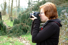 Young female photographer. Young female redhead photographer taking nature pictures Stock Image