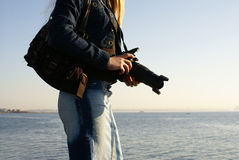 Young female photographer. Young attractive female photographer on a beach royalty free stock images