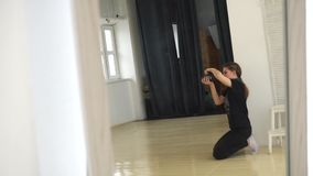 Young female photographer in black clothes sitting on the floor and taking pictures in professional photo studio. Media. Young female photographer in black stock video