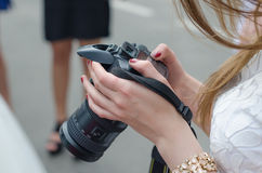 Young female photographer with camera. Royalty Free Stock Images