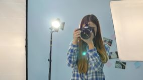 Young female photographer with camera in professionally equipped studio.  stock footage