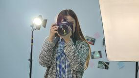 Young female photographer with camera in professionally equipped studio.  stock video footage