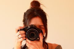 Young female photographer with camera on soft background Stock Image