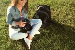 Young female photographer holding professional camera and sitting on grass royalty free stock photo