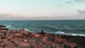 Young female photographer looking for a place to make photos at beautiful rocky seashore with huge ocean waves at sunset. Young ch. Arming female tourist taking stock footage