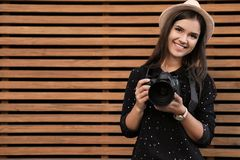 Young female photographer with professional camera near wooden wall royalty free stock photos