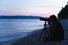 Free Young Female Photographer Sitting On The Beach With Camera On Tripod Stock Image - 181314171