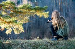 A young female photographer takes pictures of a beautiful landscape. Travel and photography. stock image