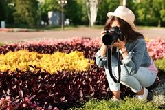 Young female photographer taking photo of flowers with professional camera stock photos