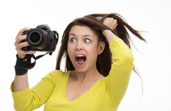 Young female photographer taking photos looking at new digital c Stock Photography